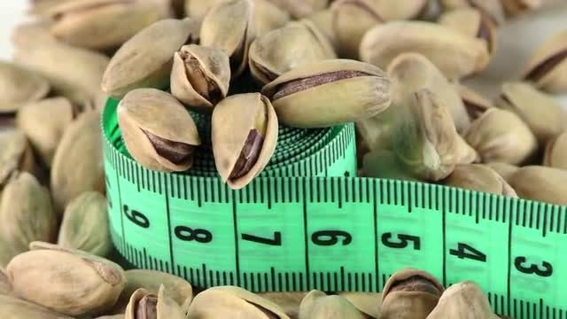 Pistachio Nuts And Measurement Tape: Stock Video
