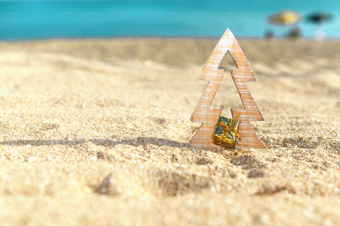 Christmas Tree With Gift On The Beach: Stock Photos
