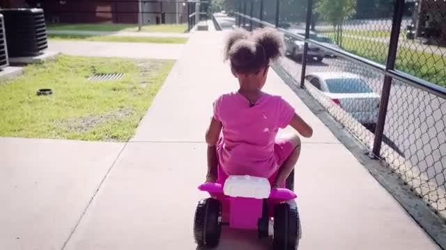 Baby girl riding electric car: Stock Video