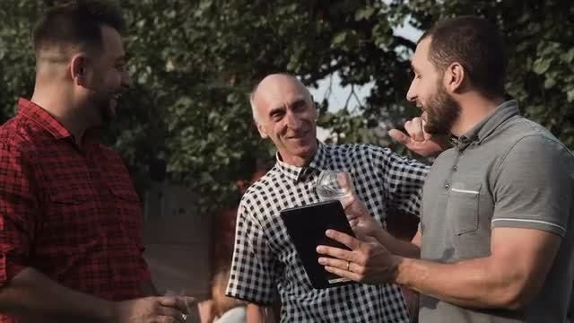 Men Discussing Something In Garden: Stock Video