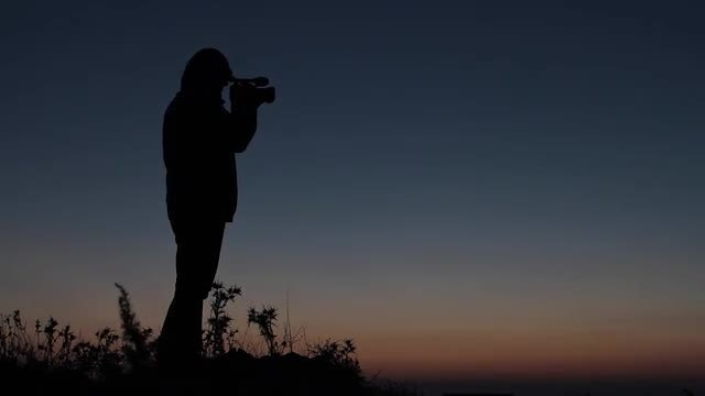 Silhouetted Man Holds Camera Outdoors: Stock Video