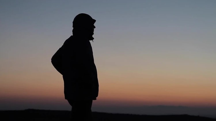 Silhouetted Man Gazing Off Mountain : Stock Video