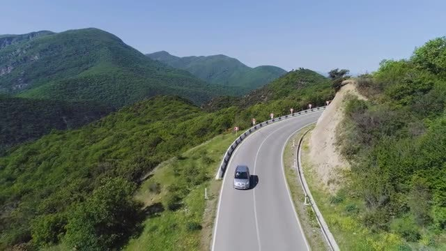 Aerial View - Car Descends Mountain: Stock Video
