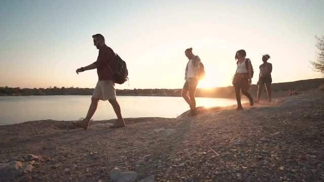 Backpackers Walking On A Coast At Sunset: Stock Video