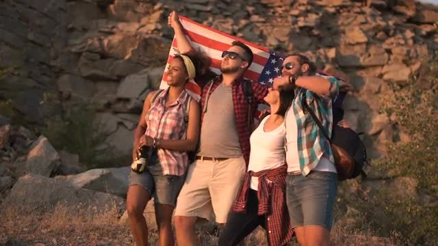 Excited Friends Posing Among Rocks With American Flag: Stock Video