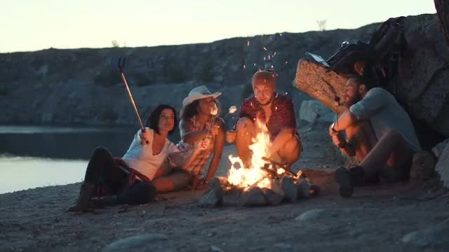 Travelers Roasting Marshmallow On Campfire: Stock Video