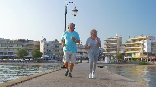Senior Couple Jogging On Pier: Stock Video