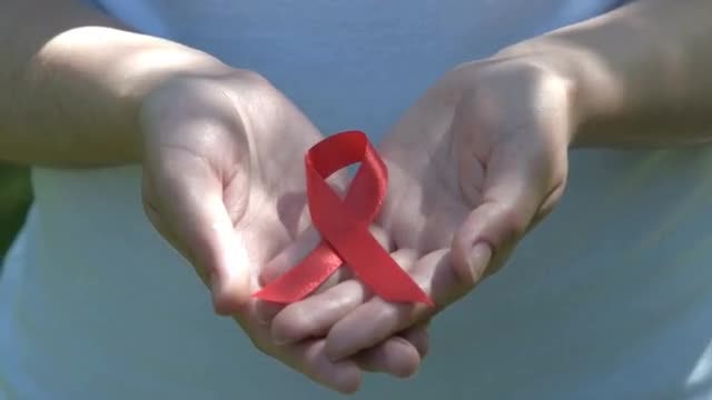 Woman Displaying Red Awareness Ribbon: Stock Video