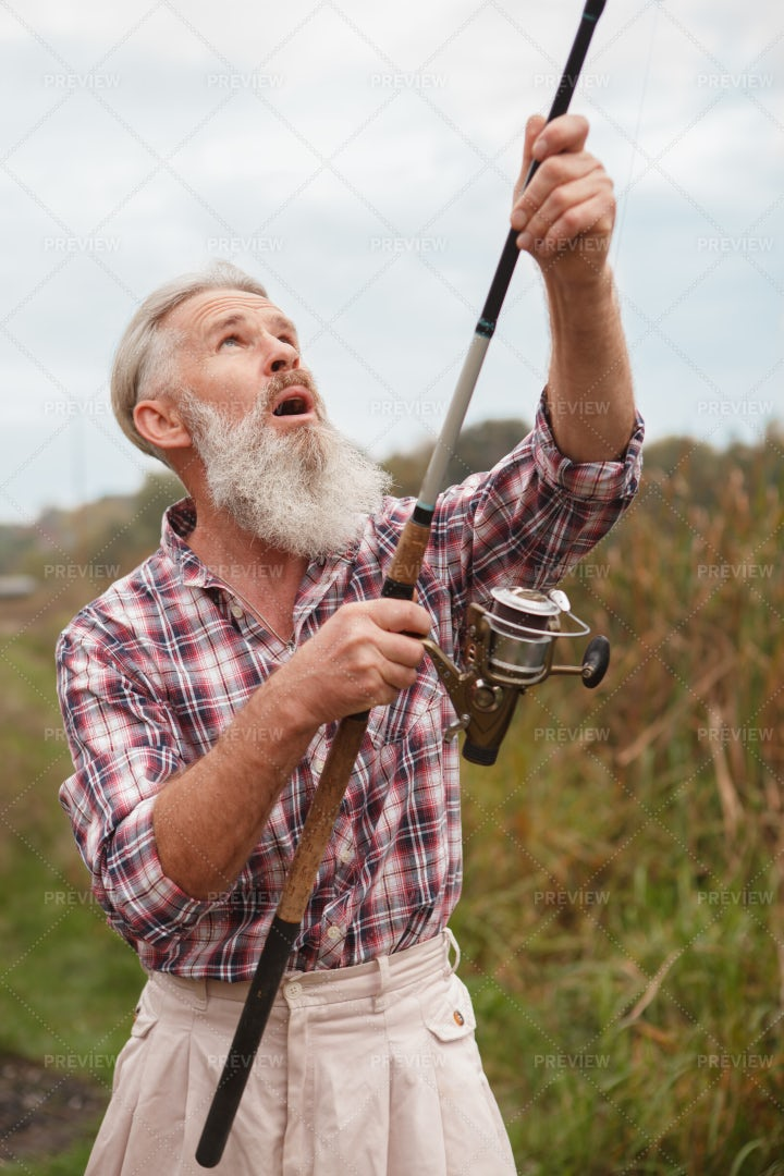 Elderly Man Preparing A Fishing Rod: Stock Photos