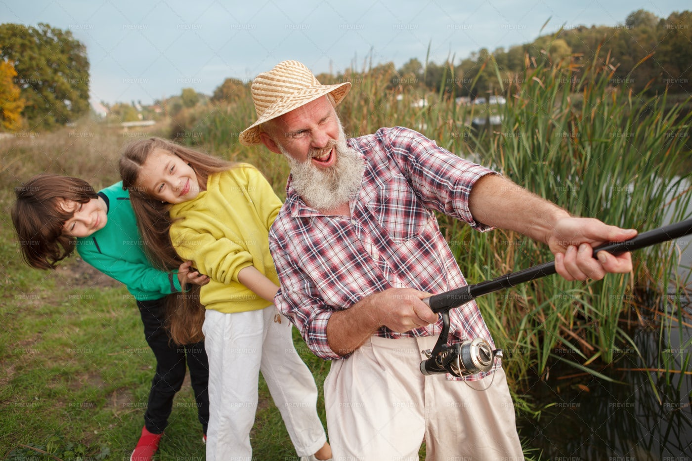 Kids And Grandpa Pulling A Fish In: Stock Photos