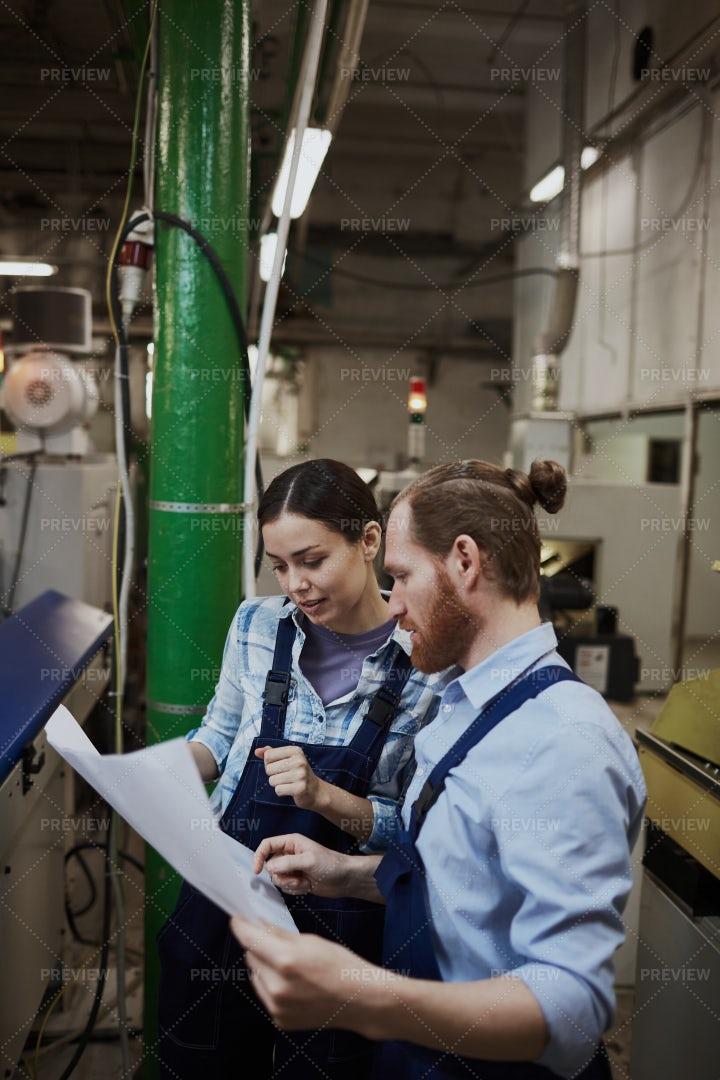 Manual Workers Examining Blueprint: Stock Photos