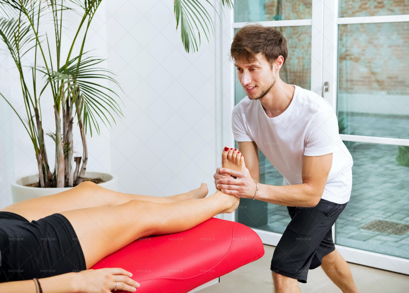 Osteopath Doing Ankle Decontraction: Stock Photos