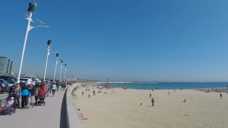 People Walking Along The Beach: Stock Video