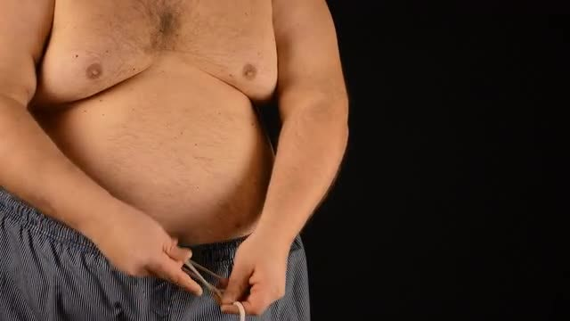 Fat Man Fastening Swimming Trunks: Stock Video