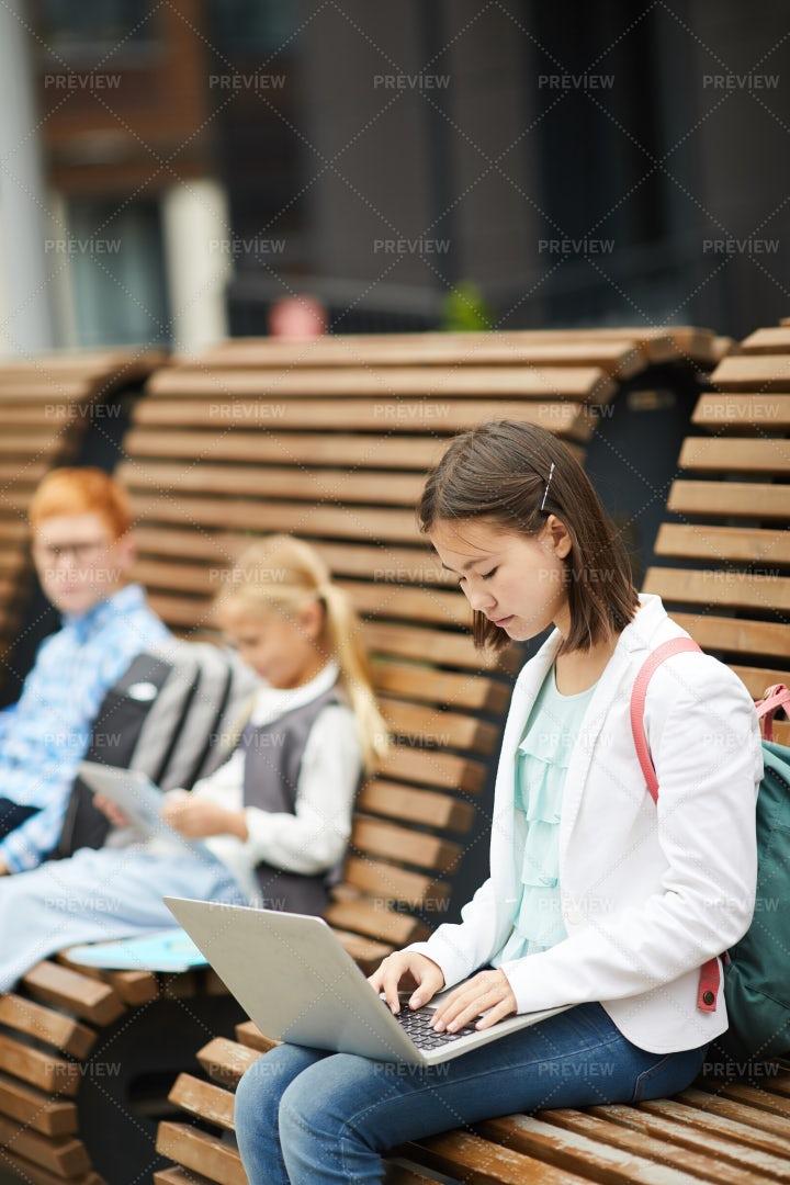 Schoolgirl Typing Outdoors: Stock Photos