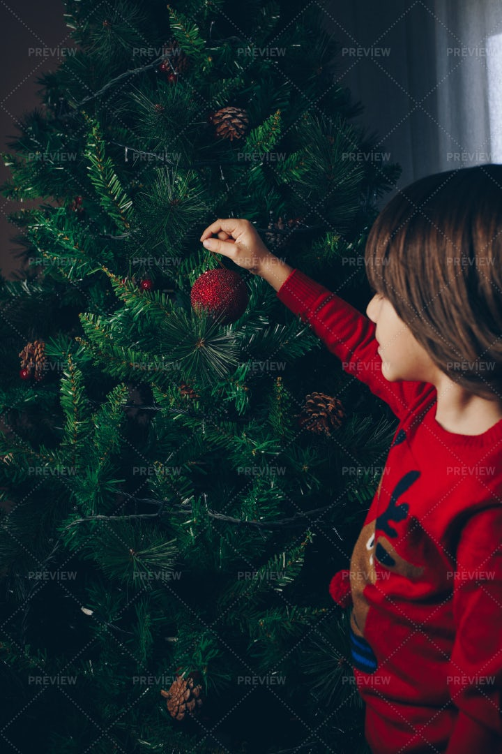 Child Placing Ornament On Christmas Tree: Stock Photos