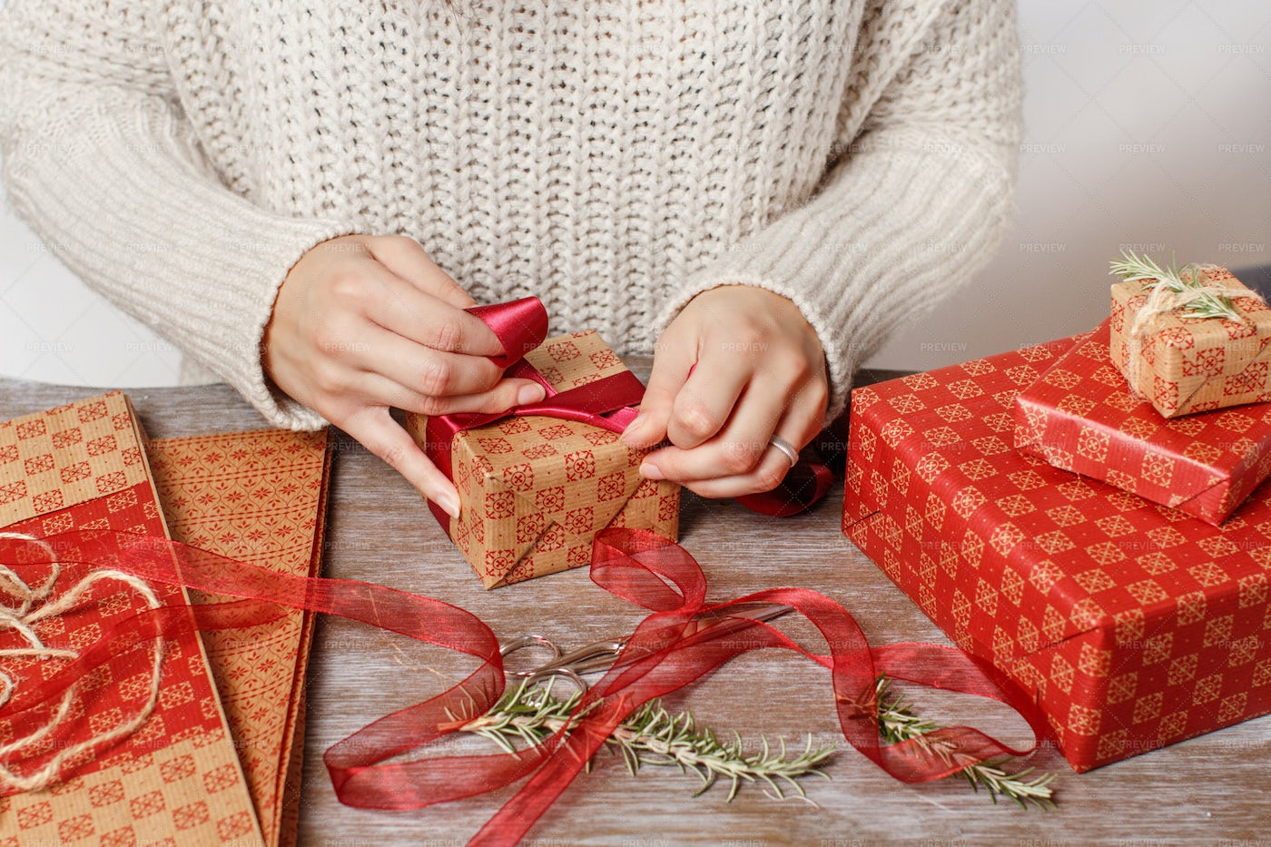 Woman Wrapping Present On Table: Stock Photos