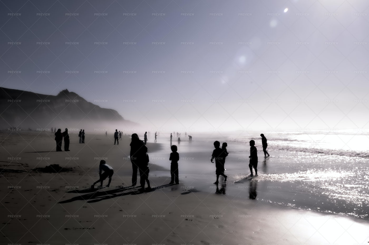 Silhouettes Of Kids Playing At Beach: Stock Photos
