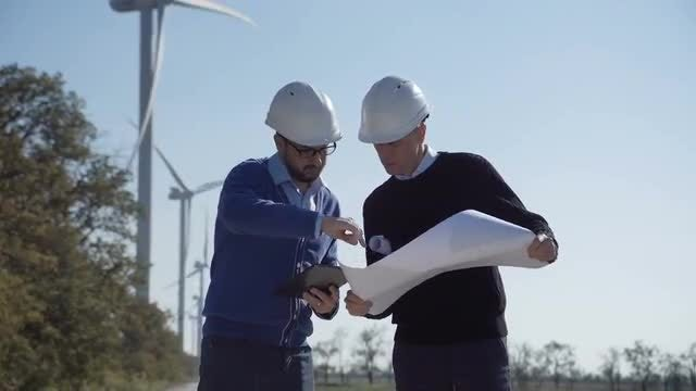 Two Engineers Discussing Wind-farm Blueprint: Stock Video