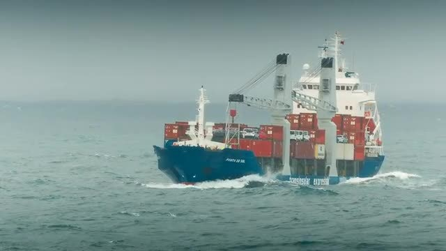 Container Ship Negotiating Rough Tides: Stock Video