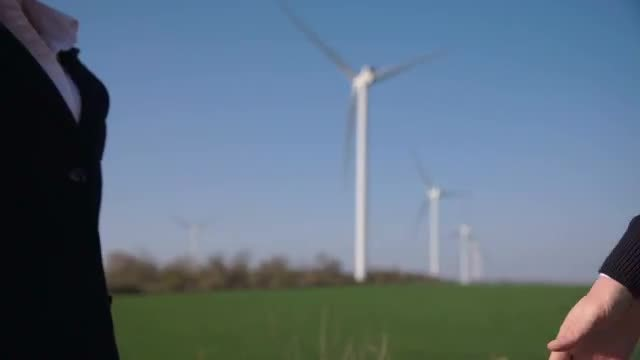 Business Handshake With Wind Turbines: Stock Video