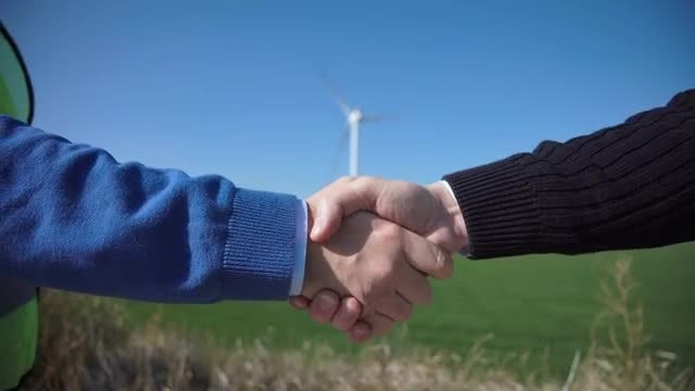 Handshake Over Wind Turbines: Stock Video