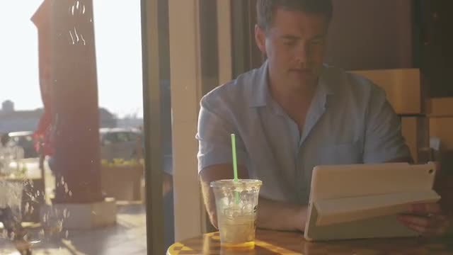 Man Using Tablet In Cafe: Stock Video