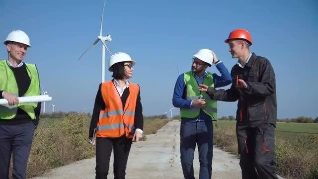Engineers Walking By Wind Turbines: Stock Video