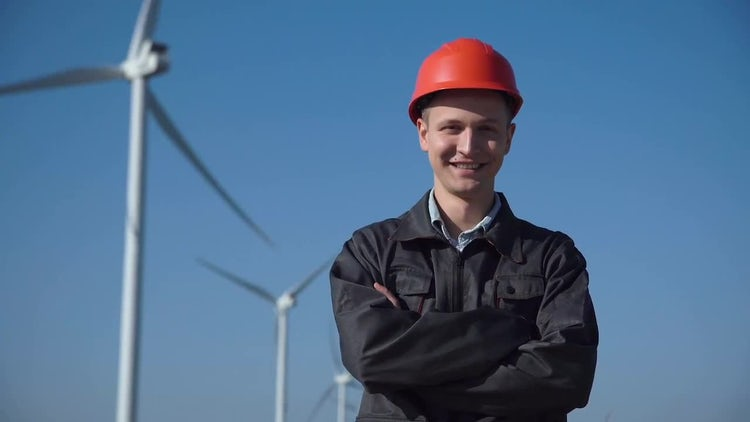 Smiling Engineer Standing Against Wind Farm: Stock Video
