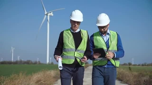 Two Wind Farm Engineers Walking: Stock Video