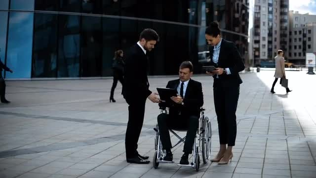 Businessman In Wheelchair Signing Documents: Stock Video