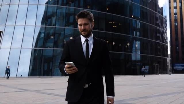 Young Businessman Using Smartphone Outdoors: Stock Video