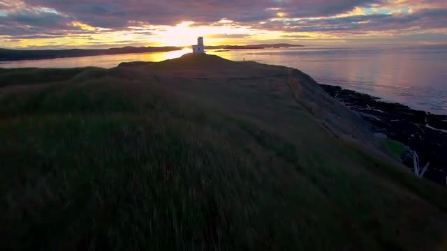 Aerial View of a Pacific Northwest Lighthouse at Sunrise: Stock Video
