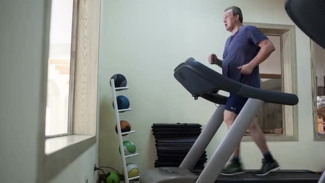 Senior Man Running On Treadmill: Stock Video