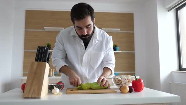 Male Cook Cutting a Zucchini: Stock Video