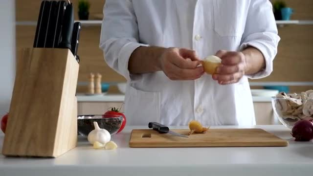 Male Cook Peeling And Cutting Onion: Stock Video