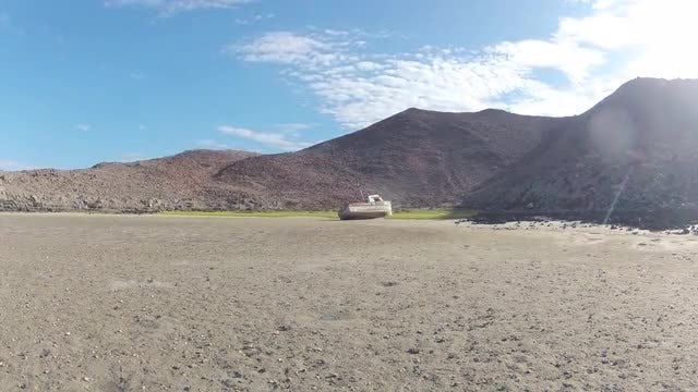 Time Lapse of Beached Boat with Mountain Range: Stock Video