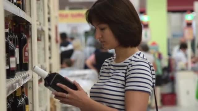 Woman Buying Wine In Store: Stock Video