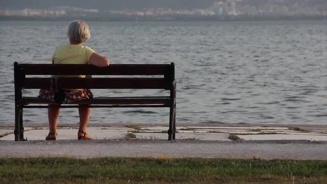 Older Woman Sitting On A Bench By The Sea: Stock Video