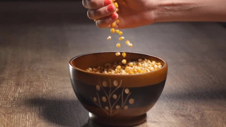 Woman Pouring Popcorn Into Bowl: Stock Video
