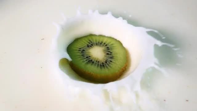 Kiwi Dropped Into Milk: Stock Video