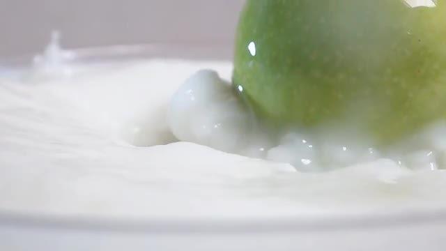Green Apple Falling Into Milk: Stock Video