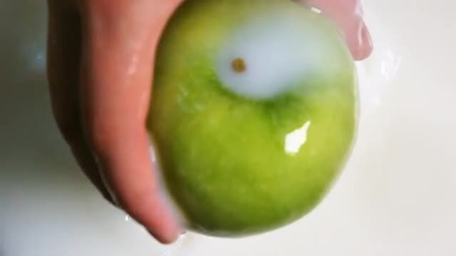 Pulling Green Apple From Milk: Stock Video
