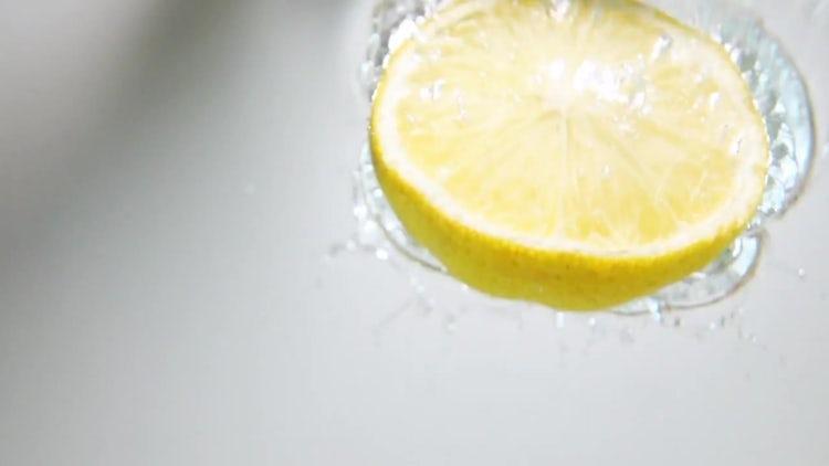 Half Lemon Drop Into Water: Stock Video