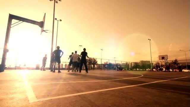 Men Playing Basketball At Sunset: Stock Video