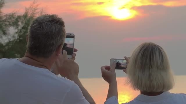 Couple Recording Sunset With Smartphones: Stock Video