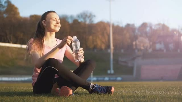 Girl Drinking Water In Stadium: Stock Video