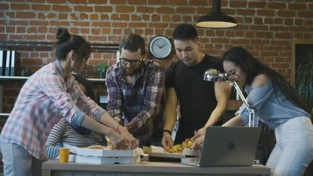 Workmates Eating Pizza In Office: Stock Video