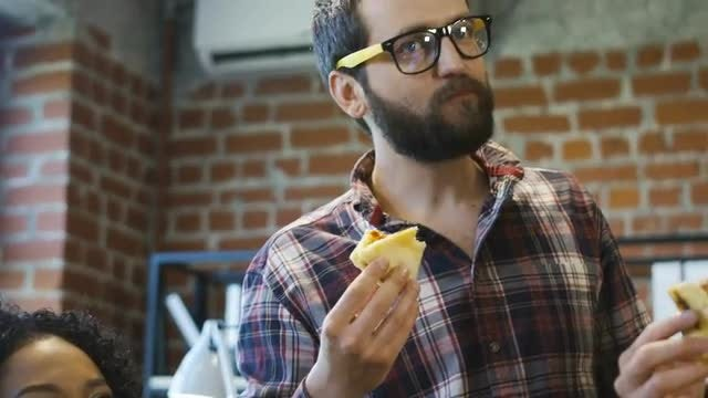 Colleagues In Office Eating Pizza : Stock Video
