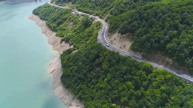 Aerial View of Cars Driving By A Lake: Stock Video